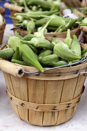 bushel: Bushel basket of fresh okra for sale on white table at farmer s market