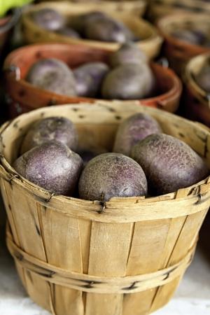 bushel: Bushel baskets of fresh purple potatoes on white table for sale at framer s market