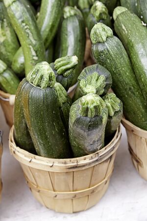 Bushel baskets of green zucchini on white table for sale at farmer s market