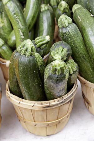 bushel: Bushel baskets of green zucchini on white table for sale at farmer s market