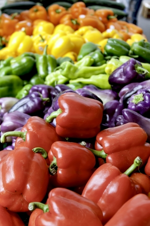 Rainbow of fresh bell peppers in colorful display at farmer s market portrait orientation Stock Photo