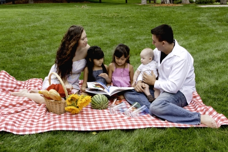 Family Having Picnic in the Park and Reading Book in the Park photo