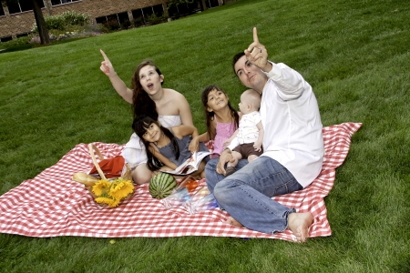 Family Having Picnic in the Park and Watching the Sky photo