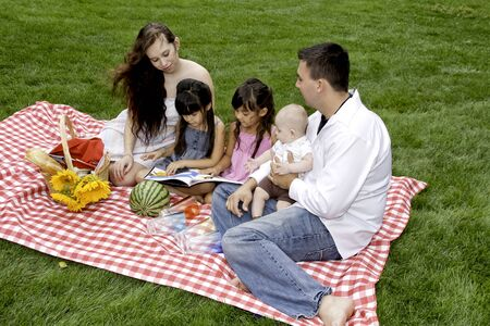 Family Having Picnic in the Park Together photo