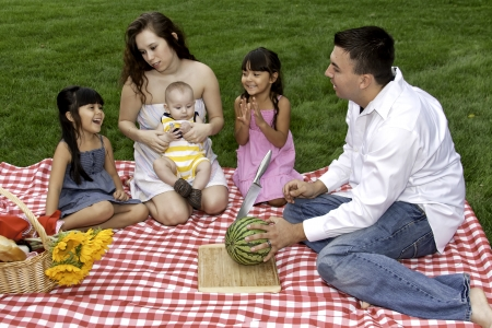 Family Having Picnic and Fun in Park photo