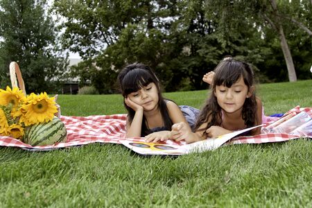 Two Girls Reading a Book on Picnic Blanket in Park photo