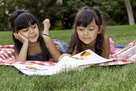 Two Girls Reading a Book on Picnic Blanket in Park Close up photo