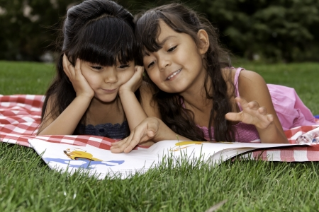 Close up of two Girls Reading a Book on Picnic Blanket in Park photo