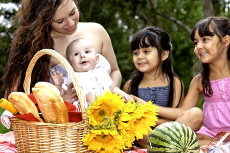 Mom, Baby and Two Girls having picnic in park photo