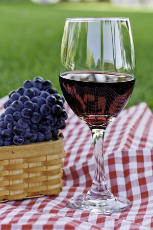 Glass of wine and basket of red wine grapes in the park photo