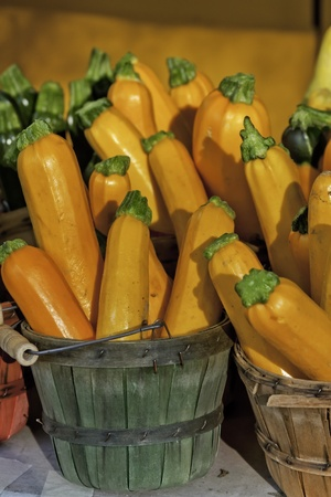 Yellow and gree zucchini in bushel basket at local market photo