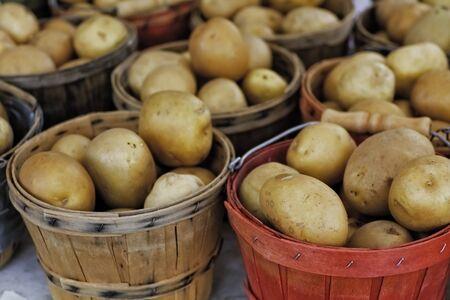 bushel: Small bushel baskets of potatoes for sale at local market Stock Photo