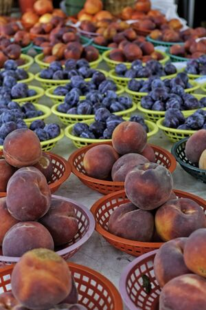 Peaches, plums and nectarines in colorful baskets for sale at local farmers market photo