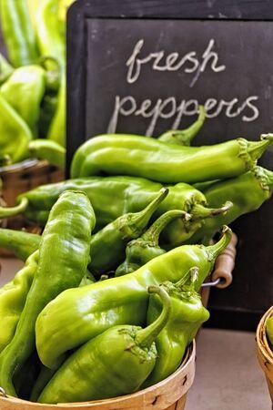 bushel: Fresh peppers in brown bushel baskets with handwritten sign on black chalkboard