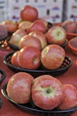 sun s: Sunlit apples in brown baskets at local market Stock Photo
