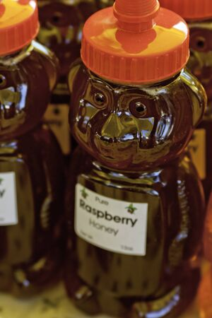 Raspberry honey in bear shaped bottle for sale at local market photo