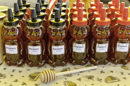 Rows of bottled honey, in bear shaped bottles with colorful caps