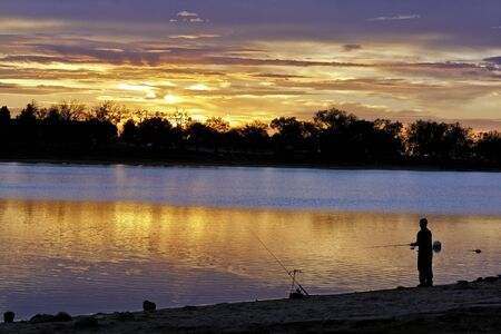 Gorgeous morning sunrise with fisherman on the shore of pond photo