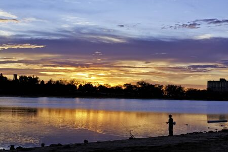 Dramatic sunrise sky with silhouetted fisherman on lake photo