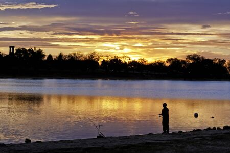 Fisherman on lakeshore fishing at sunrise photo