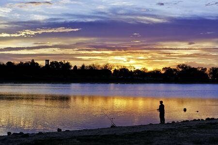 One man standing on lakeshore fishing at sunrise photo