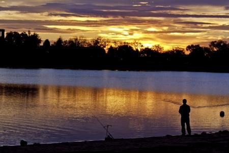 Early morning fisherman on lake shore during sunrise photo
