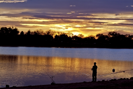 Silhouette of man fishing during dramatic morning sunrise