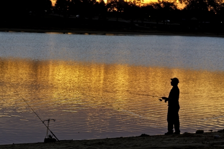 Silhouette of fisherman fishing on shore of lake at sunrise Stock Photo