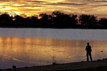 Man with 2 fishing poles fishing on shore of lake photo