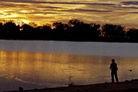 Dramatic sunrise with man fishing on shore of lake photo