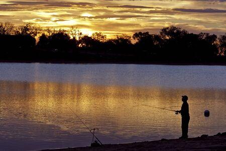 hombre pescando: El hombre pesca durante el amanecer ma�ana temprano dram�tico Foto de archivo