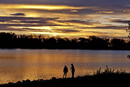 Children playing in the water on lake during dramatic sunrise