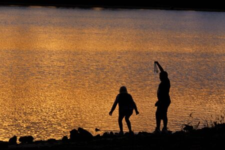 Boy and girl searching for frogs in lake during sunrise photo