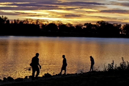 Fisherman walking past 2 children playing in the lake at sunrise