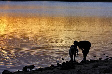 Boy and girl catching frogs on pond during sunrise photo