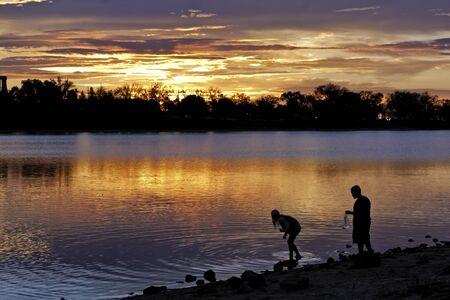 Boy and girl playing on lakeshore suring sunrise