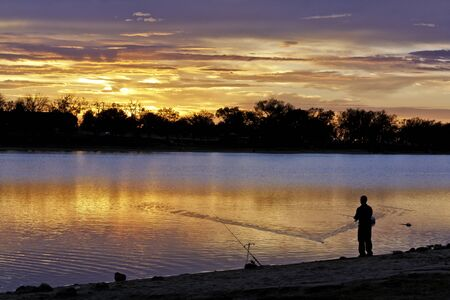 Man reeling in fishing line during dramatic lake sunrise Stock Photo