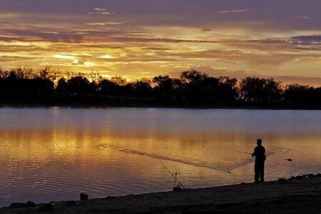 Man casting fishing line into lake during early morning sunrise photo