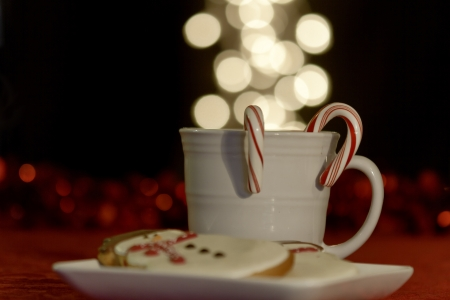White mug filled with warm drink with candy canes and snowman cookies on red table photo