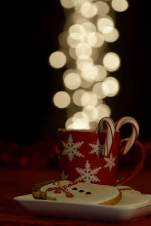 warm drink: Red snowflake mug filled with warm drink with candy canes and snowman cookies Stock Photo
