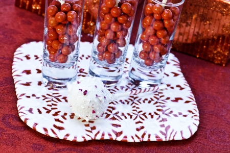 Dessert glasses filled with red candies and chocolate cake pops on peppermint candy plate photo
