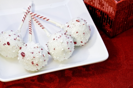 4 Christmas brownie pops covered in white chocolate on white plate Stock Photo