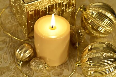 candes: Christmas ornaments, lighted candles and present in gold