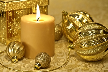 Christmas gold decorations with lighted candle on table