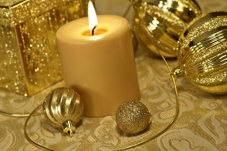 candes: Gold Christmas ornaments, present and candle on tabletop