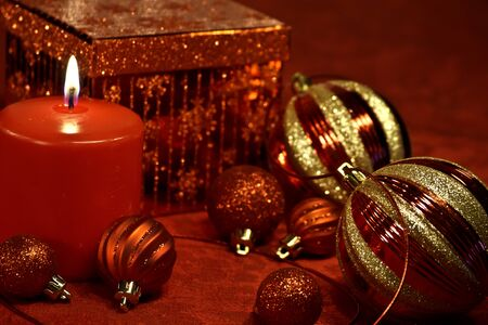candes: Red festive Christmas ornaments, candle, ribbon and present on table Stock Photo