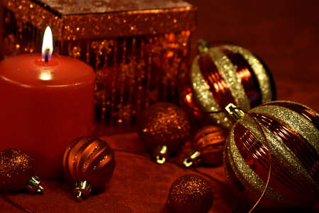candes: Red lighted candle on holiday tablecloth with Christmas ornaments and glitter present