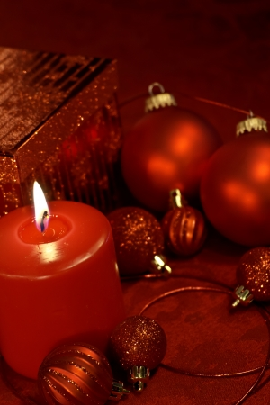 Red holiday decorations with ornaments, ribbon, present and lighted candle