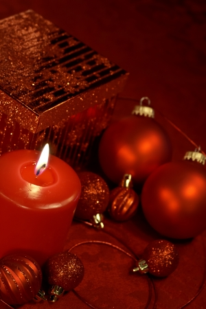candes: Festive holiday table decorated in red Christmas ornaments, present and lighted candle Stock Photo