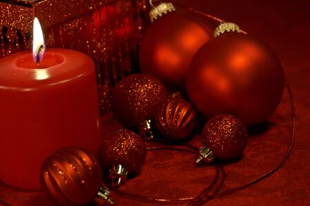 red tablecloth: Christmas decorations on red tablecloth with lighted candle